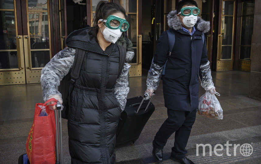 Китайская пара в защитных масках и очках выходит из поезда после того, как Всемирная организация здравоохранения (ВОЗ) объявила чрезвычайную ситуацию в связи с коронавирусом в стране. Фото Getty