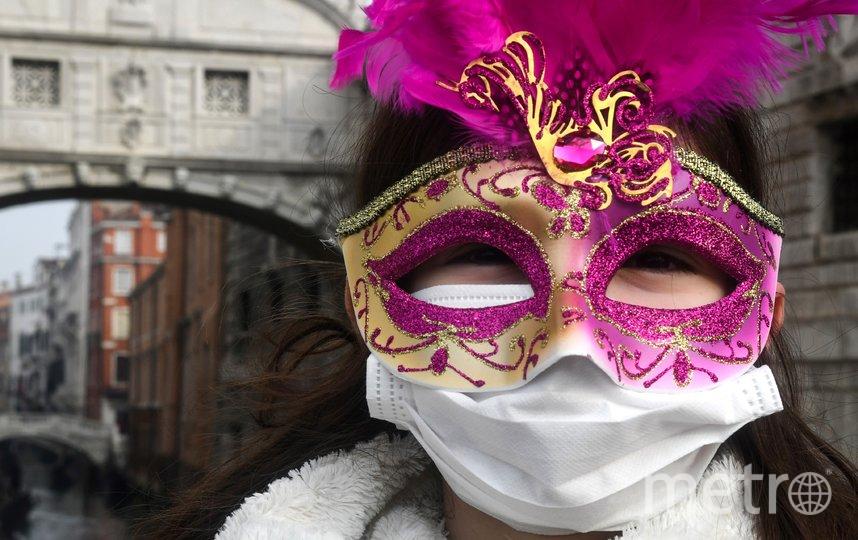 Так выглядит типичный посетитель Венецианского карнавала: под карнавальной маской – медицинская. Фото AFP
