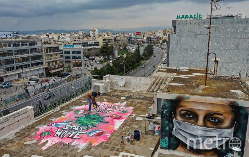 Коронавирус вдохновляет стрит-арт художников. Граффити в Афинах. Фото AFP