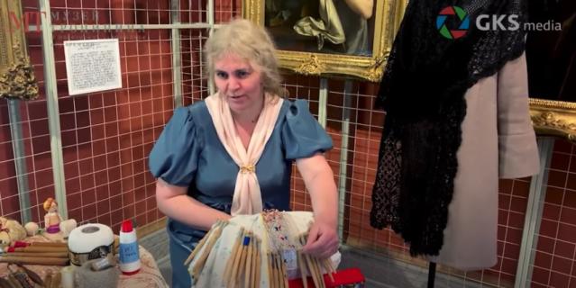 """Наталья Рычкова рассказывает о плетении на коклюшках на фоне картины """"Кружевница""""."""