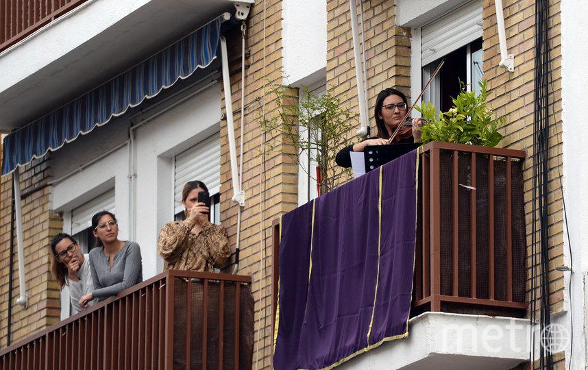 Играют на скрипке для соседей. Севилья,  Испания. Фото AFP