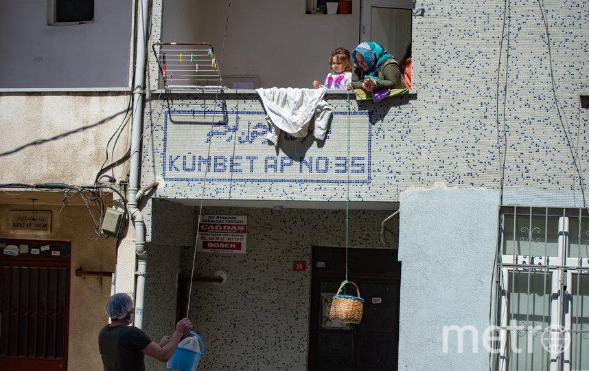Получают продукты: Пекарь кладет хлеб в корзину, спущенную женщиной с ее балкона. Стамбул, Турция. Фото AFP