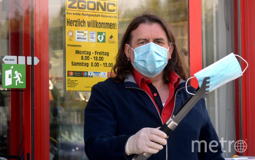 Продавец в Зальцбурге протягивает маску для лица покупателю. Фото AFP