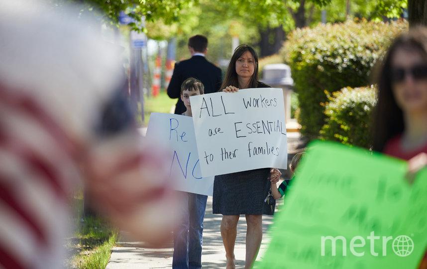"""Акция протеста в Северной Каролине. Надпись гласит: """"Все работающие необходимы для своей семьи"""". Фото AFP"""