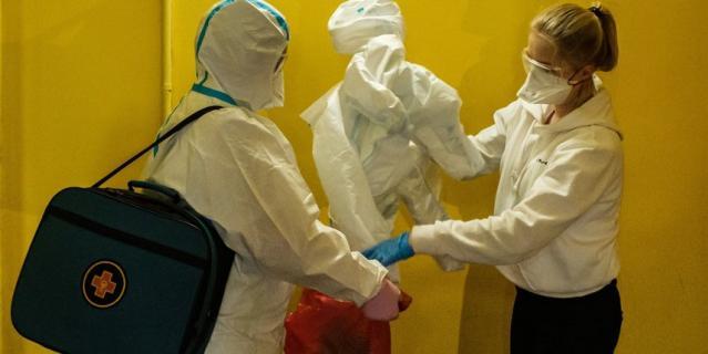 Медсестра проводит дезинфекцию костюма терапевта после посещения квартиры, где находится пациент с подозрением на коронавирус.