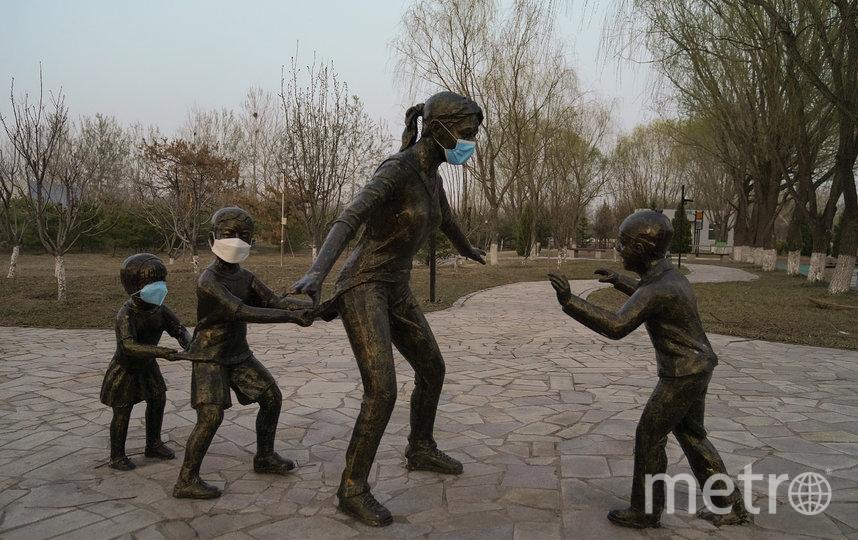 Жители Пекина использовали памятник, чтобы показать важность ношения маски. Фото Getty