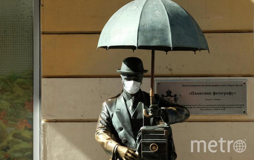 Памятник фотографу с надетой медицинской маской на Малой Садовой улице в Санкт-Петербурге. Фото РИА Новости