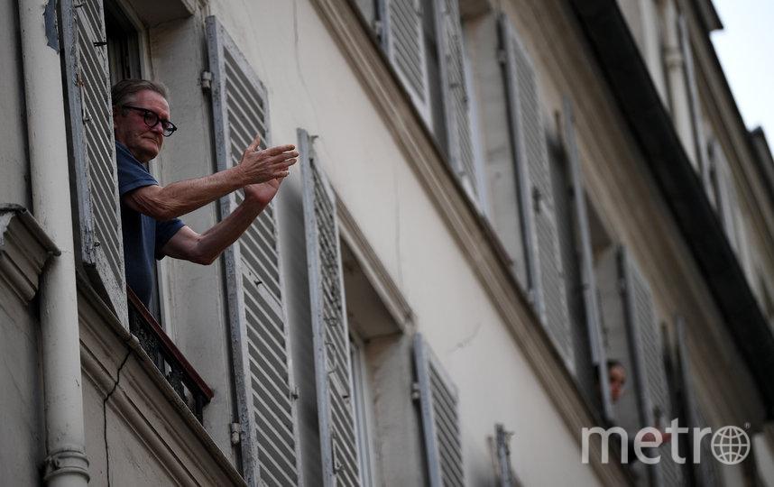 Житель Парижа аплодисментами благодарит врачей за работу из окна своей квартиры. В России такого пока наблюдать не приходится. Фото AFP