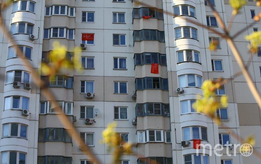 """Жители некоторых домов вывесили на окнах и на балконах Знамя Победы. Фото АГН """"Москва""""/Сергей Ведяшкин"""