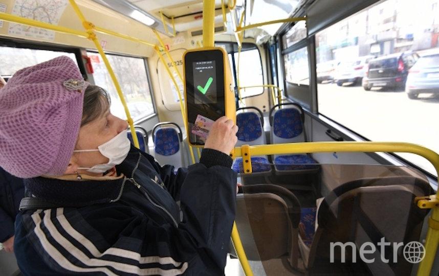Женщина в защитной маске прикладывает социальную карту москвича к валидатору в салоне городского автобуса в Москве (архивное фото). Фото РИА Новости