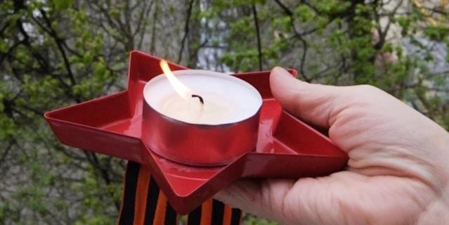 Свеча и георгиевская ленточка в руке жителя Москвы.