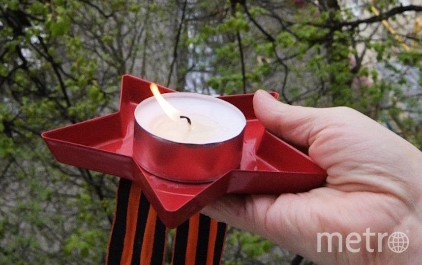 Свеча и георгиевская ленточка в руке жителя Москвы. Фото РИА Новости