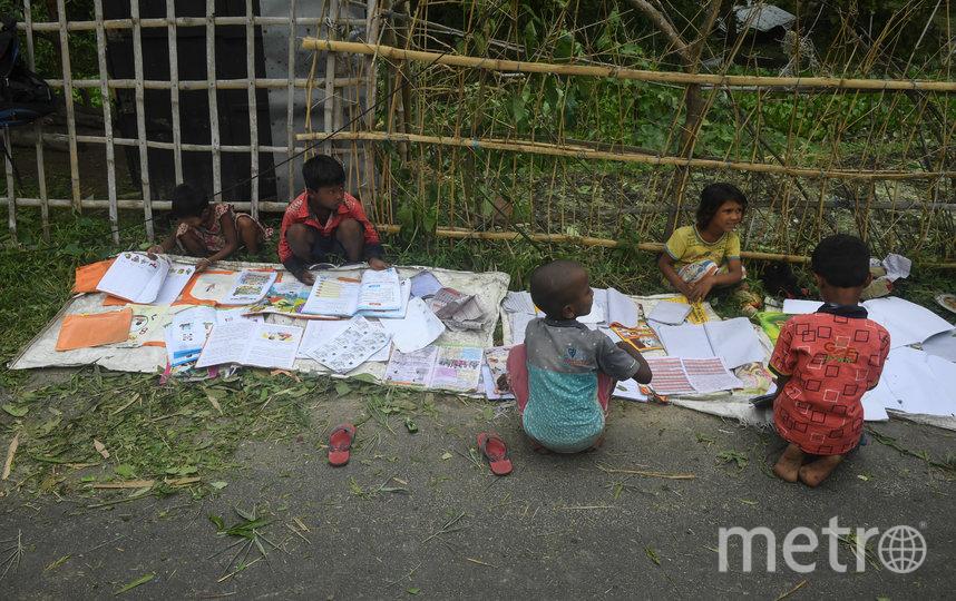 Дети, лишившиеся крова, сушат промокшие учебники. Фото AFP