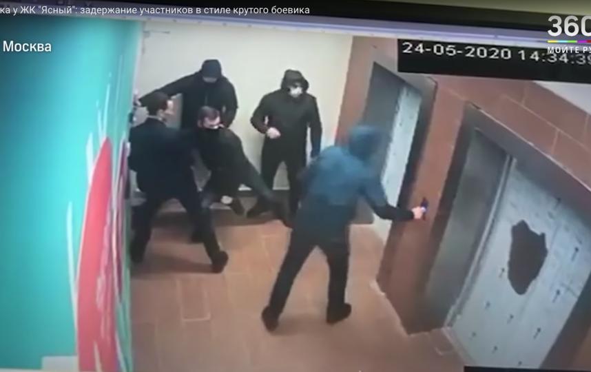 Несколько участники конфликта попыталось уехать на лифте, но им это не удалось. В следующий момент их задержал вооружённый сотрудник полиции. Фото скриншот видео телеканала 360