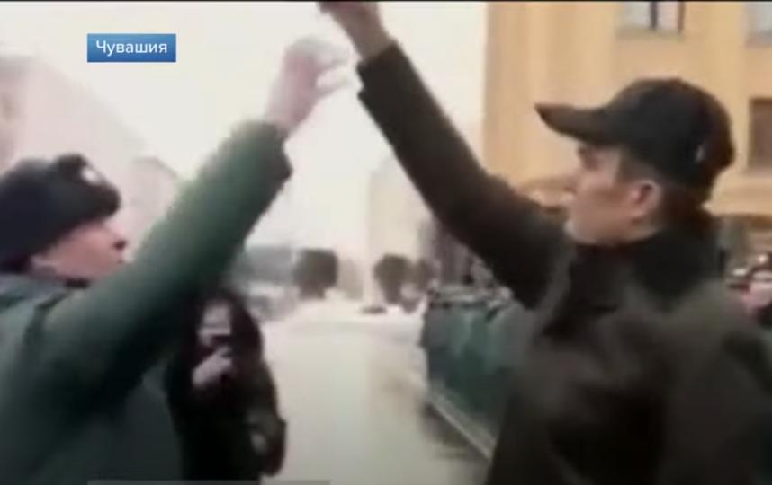 Офицер МЧС прыгает за ключами от техники в руке у Игнатьева. Фото Скриншот Youtube Первого канала