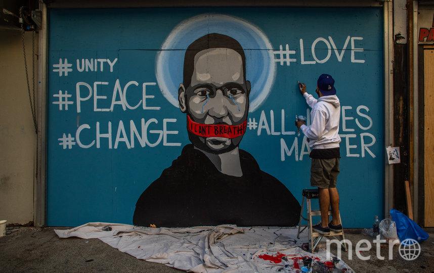 """Вокруг портрета на стене также написаны слова """"любовь"""", """"единство"""", """"мир"""", """"перемены"""" и слоган """"Все жизни имеют значения"""". Фото AFP"""