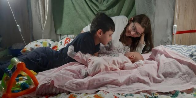 Алиса и Артём с младшей сестрой Мирой в шалаше, который они недавно научились делать из столов и одеял.