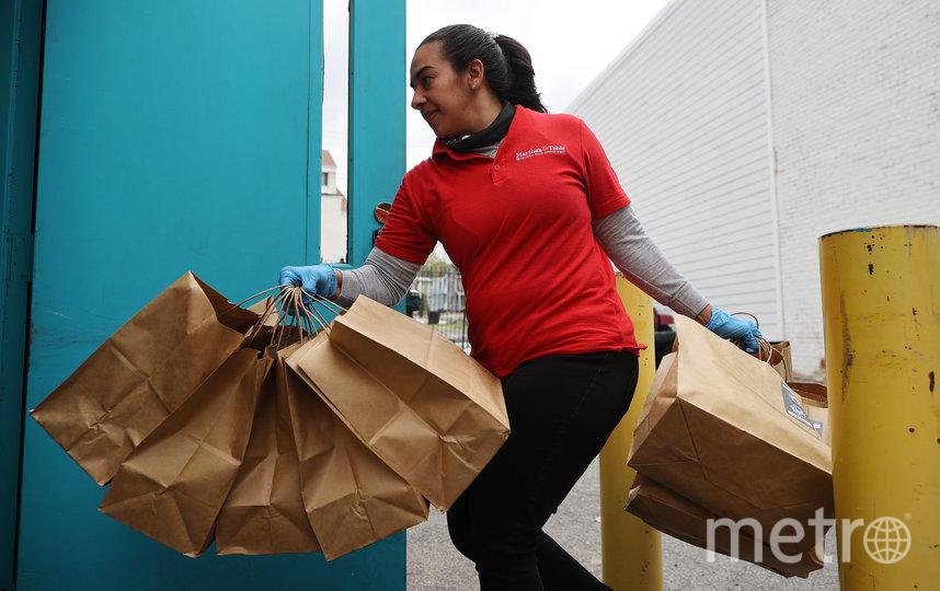 Джоанна Уильямс, координатор продуктового обеспечения во время COVID-19, выгружает сотни горячих блюд, приготовленных ресторанной группой Clyde для раздачи нуждающимся людям во время пандемии коронавируса. Эпидемия вынудила многих людей остаться без работы и здоровой пищи. Фото Getty