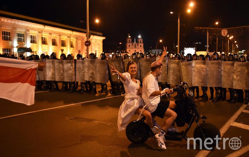 Молодожёны на скутере показывают знак мира протестующим и силовикам. Фото AFP