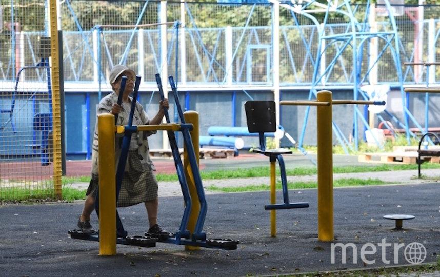 Пожилая женщина занимается на благоустроенной спортивной площадке около улицы Удальцова в Москве. Фото РИА Новости