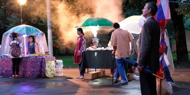 """На городской площади – праздник, среди веселящиъся людей выделяется напуганная Мухаббат, девушка в фартуке, сбежавшая из магазина. Новый день съёмок фильма """"Продукты 24""""."""