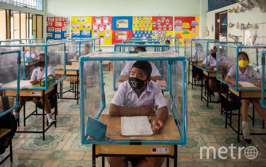 Учеников в Таиланде отгораживают друг от друга специальными кубами, но даже в них они находятся в масках. Фото Getty