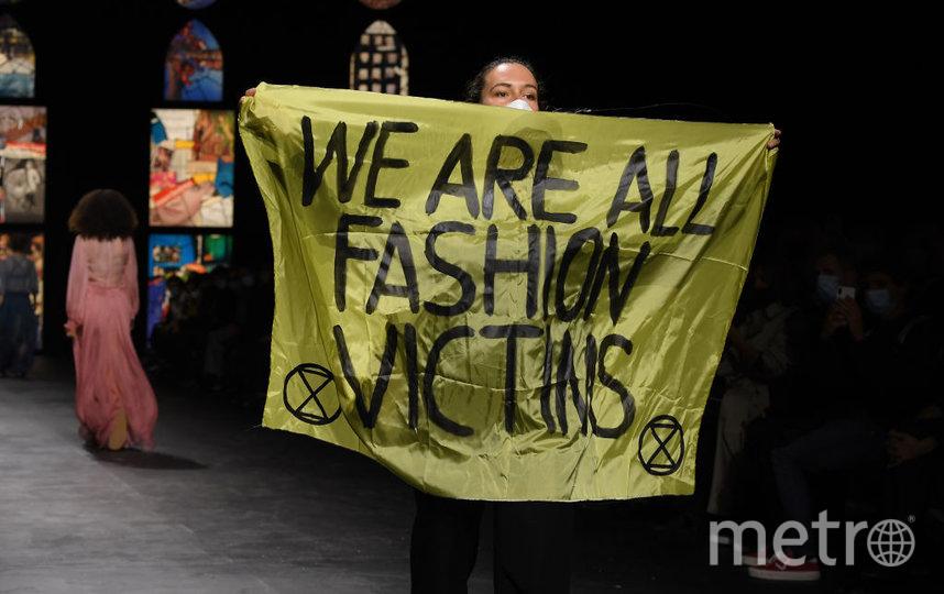 """В разгар показа на подиум выбежала женщина с плакатом """"Мы все жертвы моды"""". Фото Getty"""