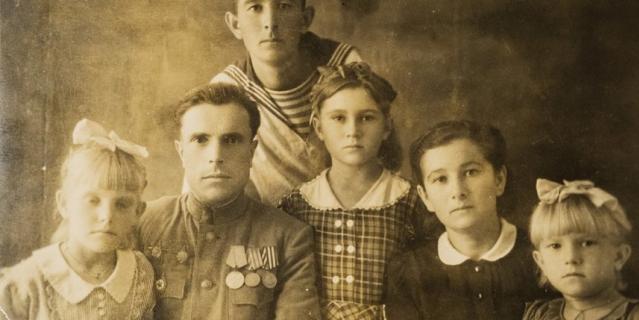 Семён Панич (в центре с медалями) с женой, дочерьми и другими родственниками.