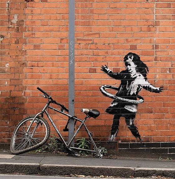 """Девочка, крутящая велосипедную шину. Фото Скриншот Instagram: @banksy, """"Metro"""""""