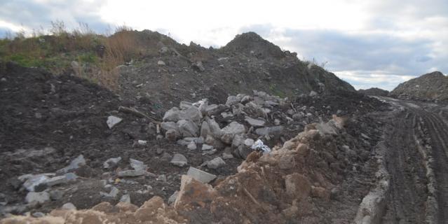 Так выглядит дорога для самосвалов в самом начале свалки. Высота некоторых мусорных гор в несколько раз  превышает человеческий рост.