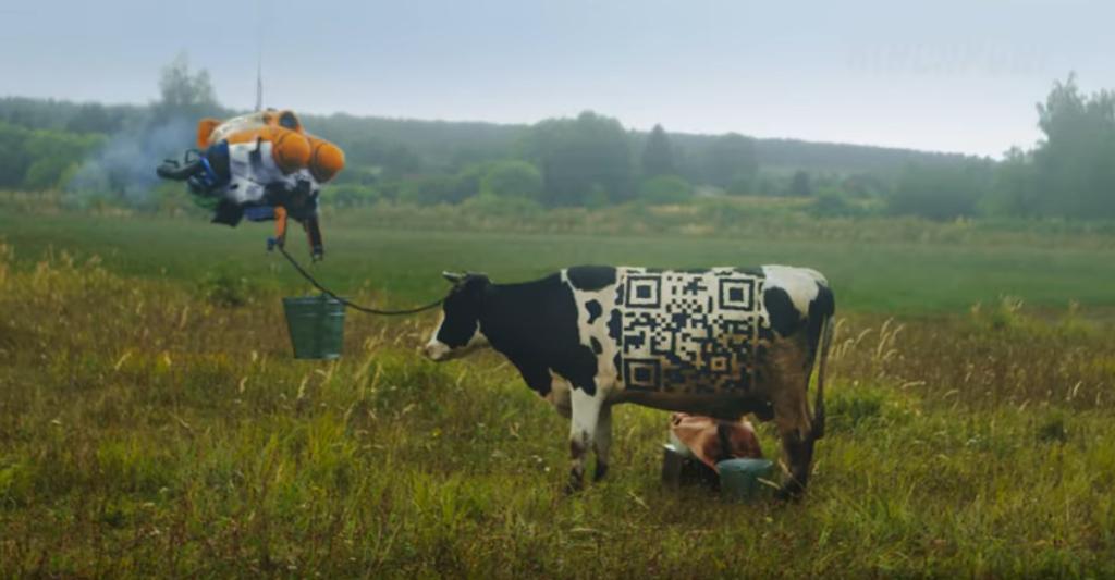 На боку у марсорусской коровы – кьюар-код, в котором зашифрована ссылка на Twitter-аккаунт Дмитрия Рогозина. А на сарае – агитплакат с его портретом и лозунгом «Сделаем Красную планету зелёной!». Фото Скриншот Youtube