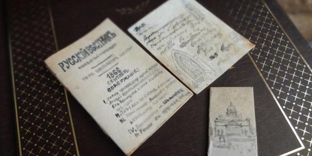 В руках у Федора Михаиловича лист в стиле его рукописеи с рисунками готических арок и журнал Русскии вестник.