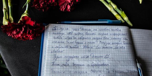 Горожане кладут цветы около снимка и оставляют записи в книге.