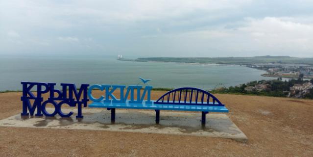 На этой скамеечке фотографируются туристы. А на заднем плане виднеется уже и сам мост.