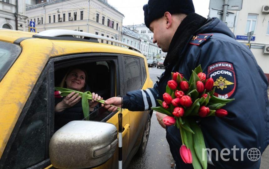Сотрудник полиции поздравляет женщину с 8 марта. Фото РИА Новости