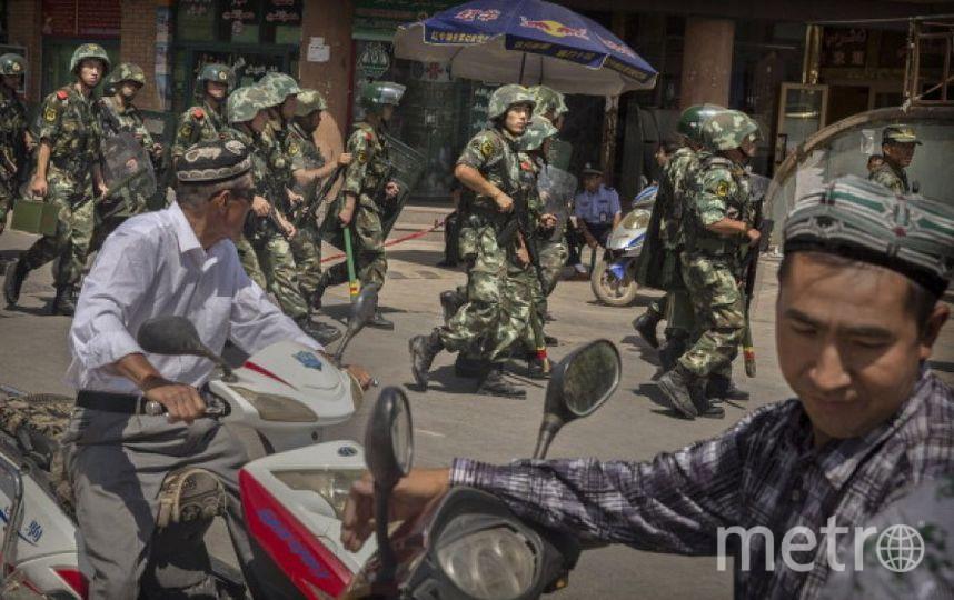 Жители Синзцяна и китайские военные. Фото Getty