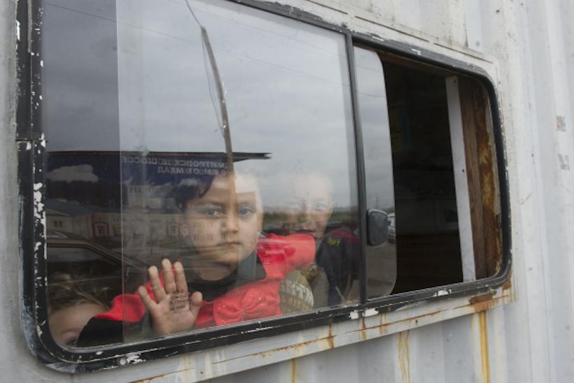Ребёнок в вагончике хостела для мигрантов возле Мытищинской ярмарки в деревне Челобитьево. Фото РИА Новости